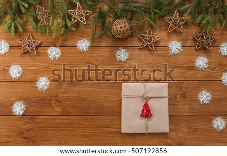 Christmas decoration, gift box in craft paper with twine rope and garland frame concept background, top view on wood table surface. Christmas ornaments and presents border with snowflakes and stars