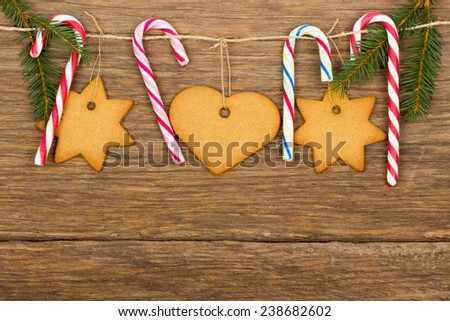 Christmas decoration - gingerbread, candy cane, rope with wood hooks and fir branches on old wooden background - stock photo
