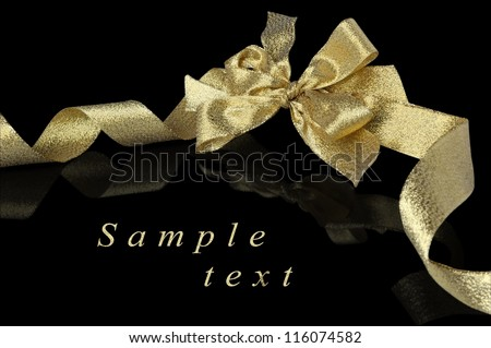 Christmas decoration - golden ribbon with bow isolated on black