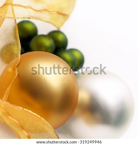 Christmas decoration; Golden, silver and green Christmas baubles with organza ribbon in close up