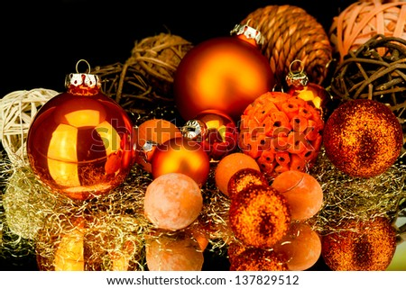 christmas decoration in orange and gold on black background - stock photo