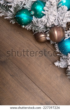 Christmas decoration like green brown and blue balls with fir  tree  branches in snow on wooden table top view close up with copy place - stock photo