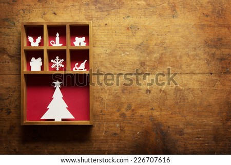Christmas decoration on a rustic or  grungy wooden wall, with plenty of copy space. Paper Christmas decoration (hand cut) in a wooden display tray.  - stock photo