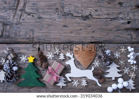 Christmas Decoration On Brown Wooden Background. Green Christmas Tree, Christmas Gift Or Present With Red Ribbon. White Reindeer, Heart, Fir Cone And Snowflakes. Shabby Chic, Rustic, Vintage Style