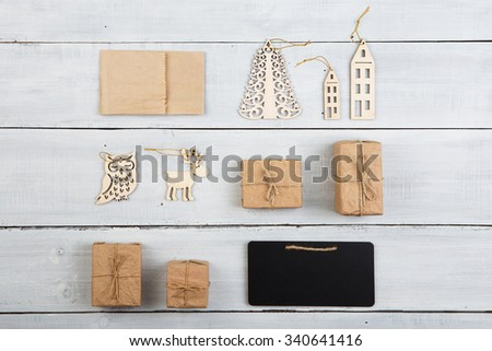 christmas decoration on wooden table - gift boxes, owl, deer, house, tree with copy space for text - stock photo
