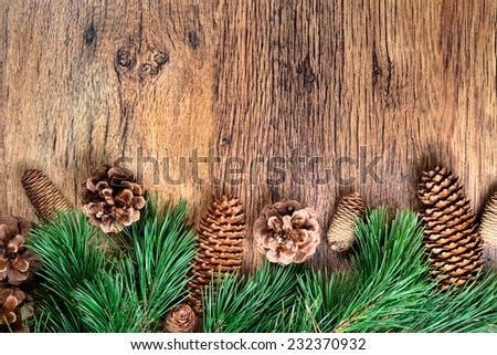 Christmas decoration - pine twigs and cones on wooden background. Space for text - stock photo