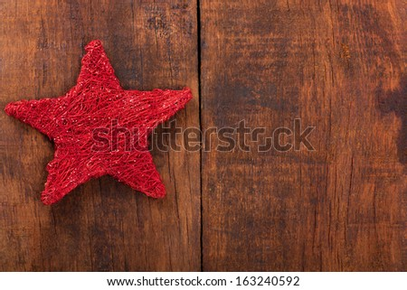 Christmas decoration.Red Christmas star on rustic dark wooden background - stock photo