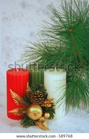 christmas decoration: red, green, white candles, branch of pine, cones, golden apple
