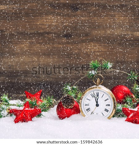 christmas decoration red stars and baubles and antique golden clock in snow over wooden background. vintage style picture with falling snow effect - stock photo