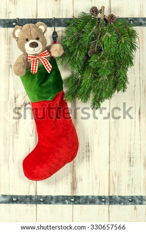Christmas decoration. Red stocking, Teddy Bear and green pine tree branch. Vintage style toned picture