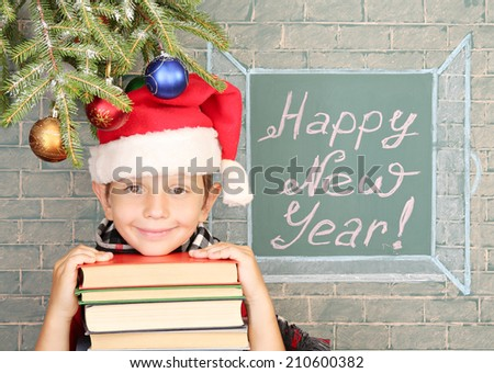 "Christmas decoration, schoolboy and message on chalkboard ""Happy New Year!"" - stock photo"