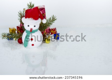 Christmas decoration - snowman on ice and snow with pine branches and gifts boxes on white background