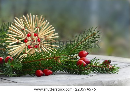 christmas decoration, straw star, rose hips and pine branch, uncluttered arrangement outside, copy space - stock photo