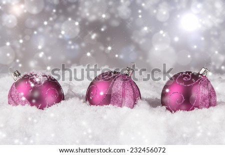 Christmas decoration, three balls on snow with abstract background