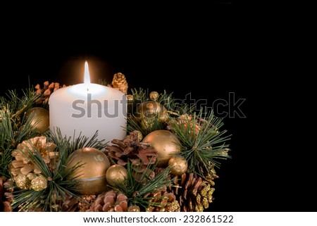 Christmas decoration with a white candle and pine apples on a black background