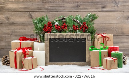 Christmas decoration with burning candles and gift boxes. Christmas tree branches in basket. Chalkboard for your text - stock photo