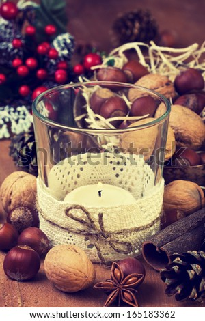 Christmas decoration with candle, nuts and spices on wooden background ( grunge ) - stock photo