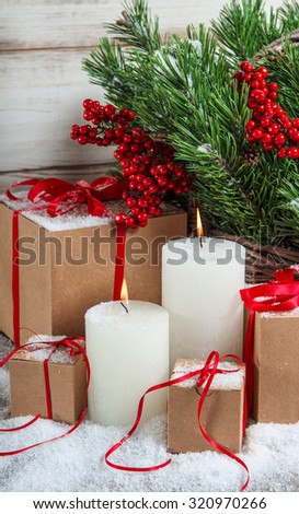 Christmas decoration with candles and gifts. Christmas tree branches with red berries - stock photo
