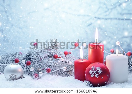 Christmas decoration with candles,fir branch and balls on snow. - stock photo