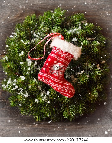 Christmas decoration with Christmas wreath and hanging stocking on snow wooden board. - stock photo