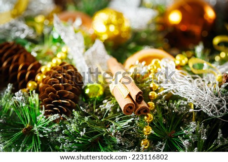 Christmas decoration with fir branches, golden and silver baubles and cones and cinnamon sticks. Holiday background. - stock photo