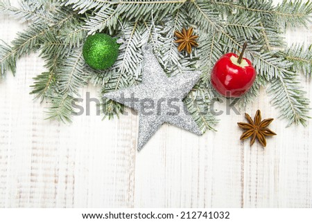 Christmas decoration with fir twigs, baubles, silver star and artificial snow with a blank space  - stock photo