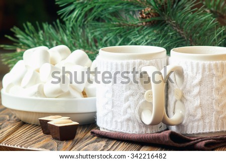 Christmas Decoration with fir twigs, chocolate candies, marshmallow and cups of hot tea dressed in knitted warm winter mug holder on wooden background - stock photo