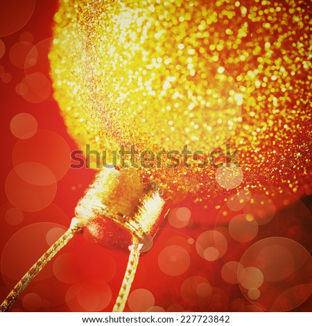 Christmas decoration with gold shiny bauble close up in bokeh lights over red background. Instagram vintage color effect. Selective focus. - stock photo