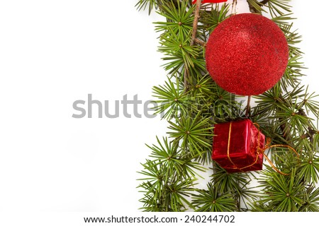 Christmas decoration with green pine or fir and red round ornament and one gift for Christmas tree. Holiday decorations isolated on white background. Empty or copy space for holiday greeting card - stock photo