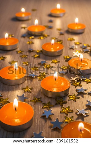 Christmas decoration with group of orange candles and yellow shining stars  - stock photo