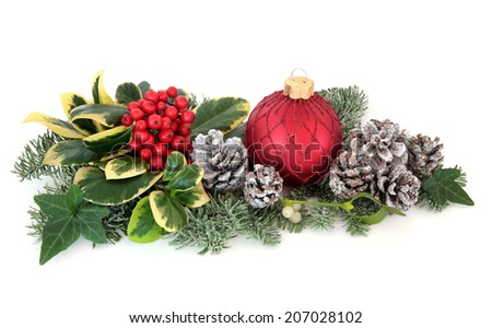 Christmas decoration with holly, red baubles, mistletoe, ivy, fir and cedar leaf sprigs with snow covered  pine cones over white background. - stock photo