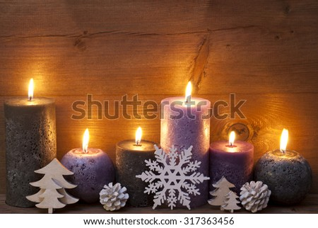 Christmas Decoration With Light Purple And Black Candles, Christmas Tree, Fir Cone, Snowflake. Peaceful Atmosphere With Candlelight. Wooden Background For Copy Space. Vintage Rustic Style - stock photo