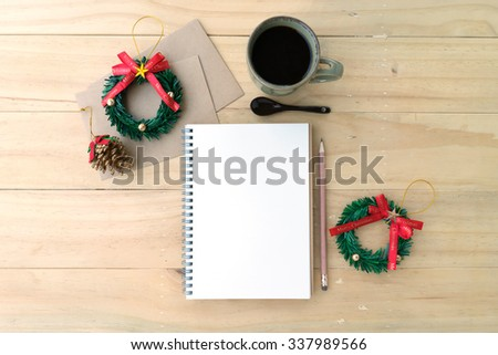 Christmas decoration with opened notebook and cup of coffee on wooden background  - stock photo