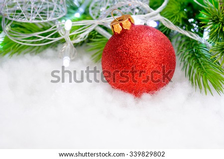 Christmas Decoration with Red Ball, Green Fir Branch and White Lights in the Snow. Greeting Card - stock photo