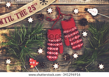 Christmas decoration with red knitted mittens, pine tree twigs and gingerbread cookies - stock photo