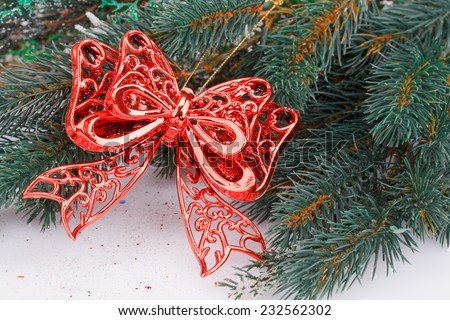 Christmas decoration with red ribbon and fir-tree branch. - stock photo
