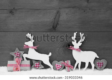 Christmas Decoration With Reindeer Couple In Love On White Snow. Christmas Gift, Present, Red Ribbon, Heart, Star. Gray, Rustic, Vintage Wooden Background. Black And White Image With Red Hotspot - stock photo