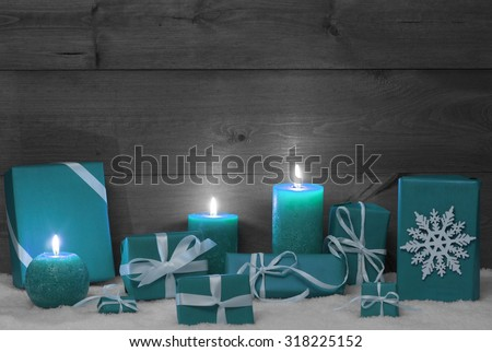 Christmas Decoration With Turquoise Candles, Handmade Christmas Gifts, Presents, Snowflake, Snow.Peaceful Atmosphere With Candlelight. Wooden,Vintage,Rustic Background.Copy Space.Black And White Image - stock photo