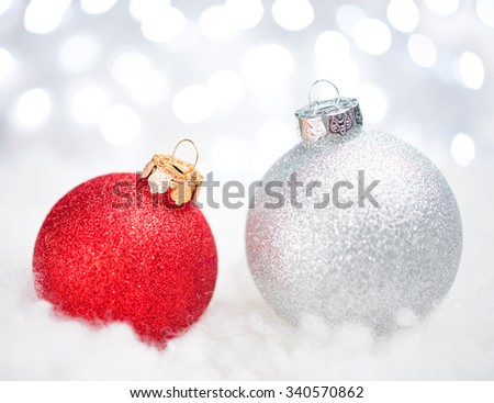 Christmas Decoration with Two Red and White Balls in the Snow on the Blurred Background of Bright Holiday Lights. Greeting Card - stock photo