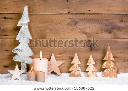 Christmas decoration:wooden trees,stars,candles and snow on wooden background - stock photo