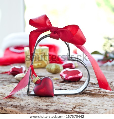 Christmas decorations and a heart-shaped cookie cutter with a red bow - stock photo