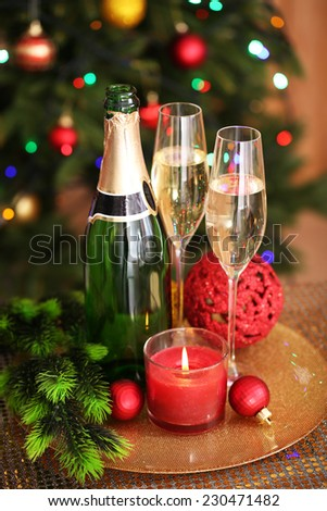 Christmas decorations and champagne bottle and glasses on bright background - stock photo