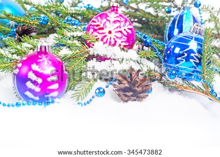 Christmas decorations and fir with pine cones on snow