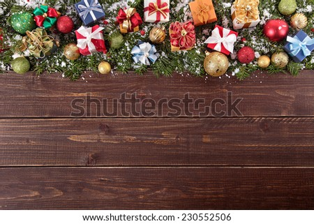 Christmas decorations and gift boxes on wooden board background with copy space - stock photo
