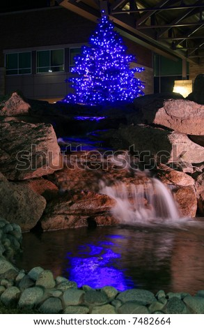 Christmas decorations and lights reflecting off of waterfall and pond - stock photo