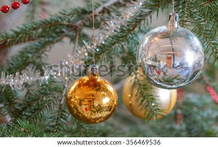 Christmas decorations hanging on a christmas tree branch. Colorful gold and silver balls. Short depth of focus - stock photo