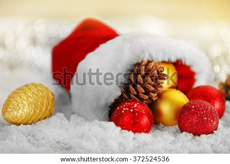 Christmas decorations in red Santa hat on shiny background, close up