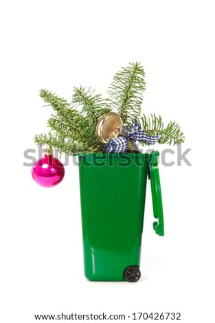 Christmas decorations in the green wheelie bin against white background - stock photo
