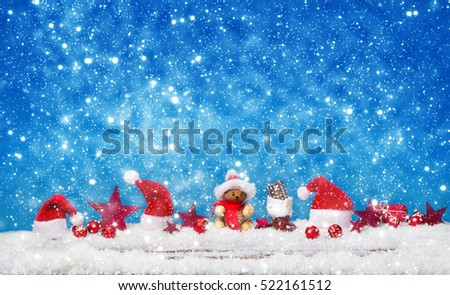 Christmas decorations in the snow against blue