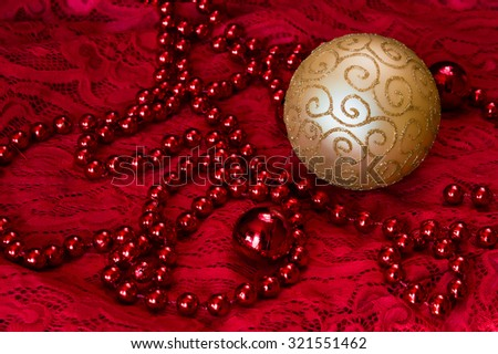 Christmas decorations on a red background Accessories. Gold Ball toy on red lace. New year toy. Toned - stock photo